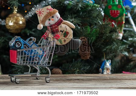Christmas Snowman pushing shopping cart with blue car in it.
