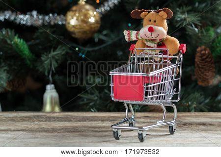Happy Christmas reindeer pushing empty shopping cart