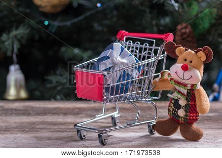 Happy Christmas character pushing shopping cart with gift