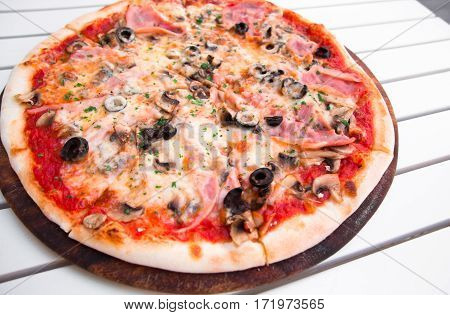 Delicious hot pizza with ham and mushrooms on wooden plate on white table