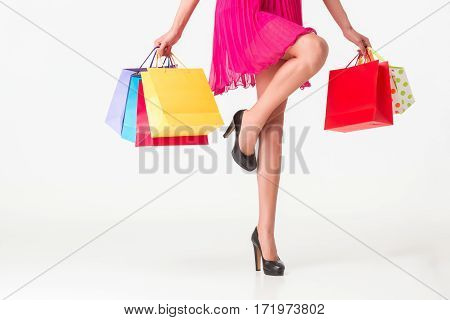 Part body, beautiful female slender legs. Sexy girl holding a paper shopping bags, isolated on white background. Woman in a pink dress
