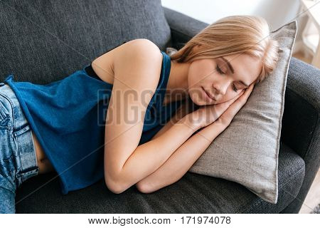 Tired fatigued young woman sleeping on couch at home