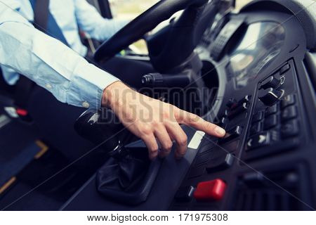 transport, transportation, tourism, road trip and people concept - close up of bus driver driving passenger bus and pushing button on dashboard