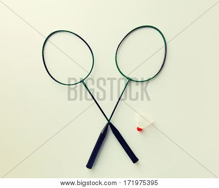 sport, fitness, healthy lifestyle and objects concept - close up of badminton rackets with shuttlecock