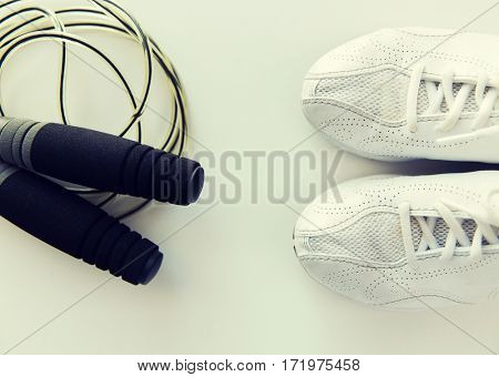 sport, fitness, healthy lifestyle, cardio training and objects concept - close up of sneakers and skipping rope