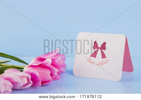 Bouquet Of Tender Pink Tulips With Greeting Card On Light Blue Wooden Background