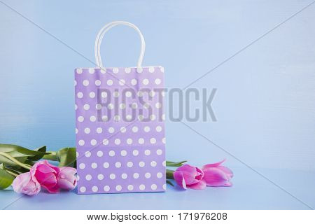 Lilac Shopping Bag With Bouquet Of Pink Tulips On Blue Wooden Background