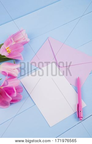 Bouquet Of Tender Pink Tulips With Empty Paper On Blue Wooden Background