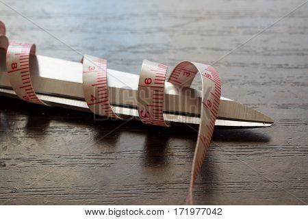 Blade of Scissors and Measuring Tape. Tape Curl around Scissors.