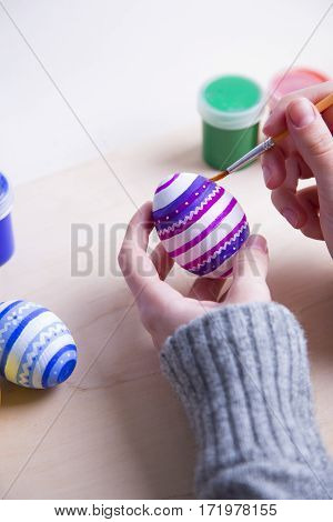 Female Hands Painting Wooden Easter Egg With Brush