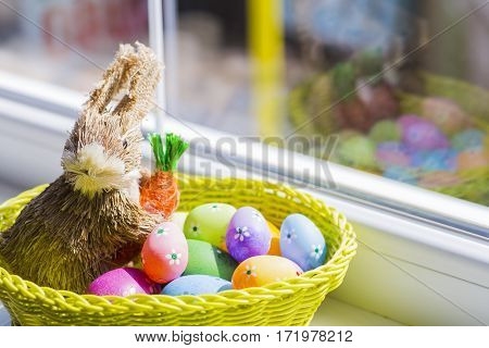 Wicker Rabbit With Colorful Easter Eggs In Basket Near Window