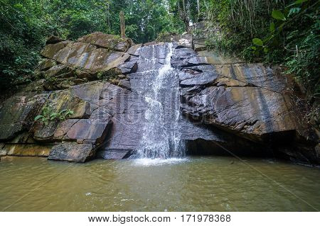Enchanting pristine Borneo jungle forest with beautiful waterfall with amazing rock pattern in Beaufort, Sabah, Borneo.