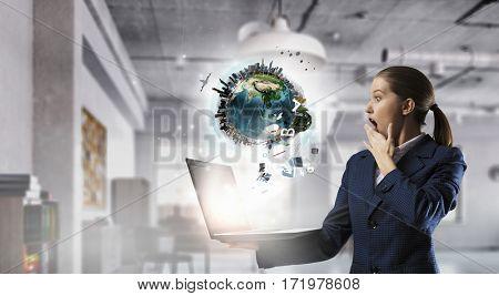 Elegant businesswoman using laptop . Mixed media