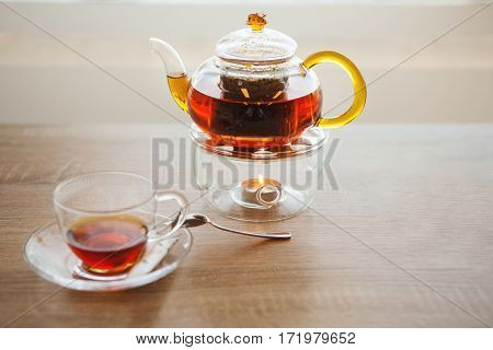 Herbal tea in glass kettle is heated small round candle. Near glass kettle is glass saucer with silver spoon on which there is third cup of tea filled system.