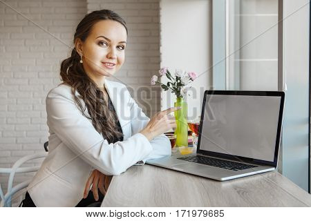 Girl pointing finger in computer monitor. Businesswoman showing something on laptop screen. Girl studing via internet. Brunette student learning with media technologies. Lady manager at workplace