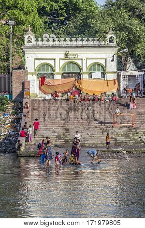 People Cleaning Clothes And Washing In The River Ganges In Calcutta