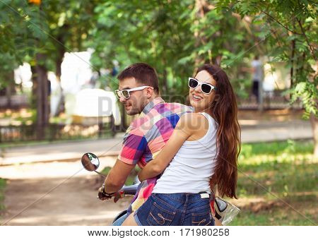 Riding A Scooter Together. Young Couple Riding A Scooter