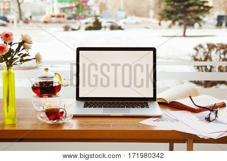 Open laptop, scribbling-book with pen, paper with graphics, glasses, kettle and cup with tea, spoon on saucer and vase with roses lying on desktop