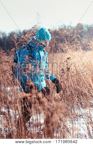 Boy Hiking Through Meadows In The Wintertime