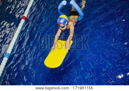 boy swimming with kickboard at swimming pool, top view