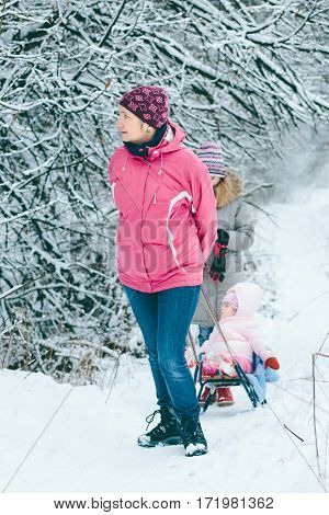 Woman Pulling Sledge With Her Little Daughter
