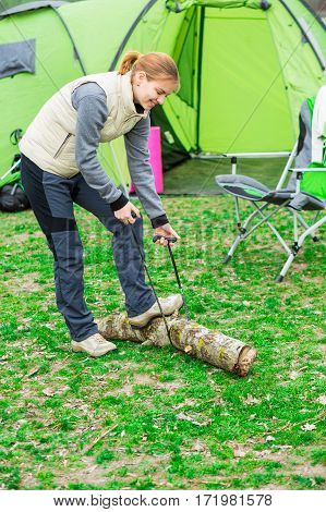 woman sawing wood for campfire using portable tourist saw. Active outdoor recreation