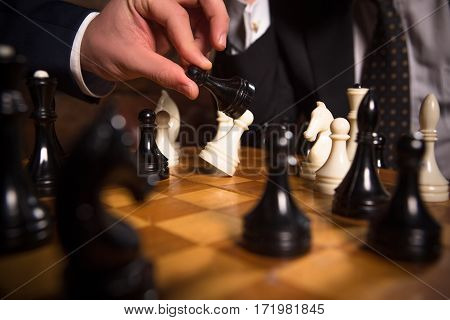 Closeup of chess pieces on chessboard. Men playing chess in restaurant. Business concept. Competition between companies, enterprises, firms.