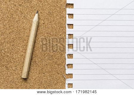 Close up of a blank notepad page with pencil on a cork surface