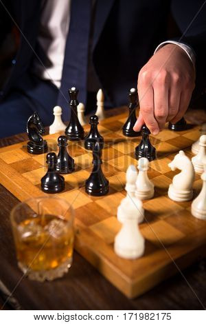 Closeup of chessboard with white and black chess pieces on. Man ready to play with partner. Business concept. Competition and rivalry concepts.