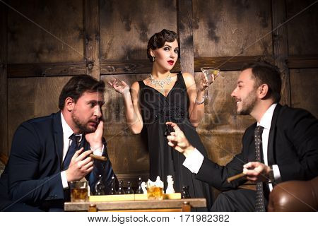 Focus on elegant lady with red lips. Rivalry or competition between two businessmen fighting for woman while playing chess.