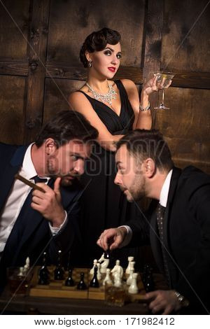 Rivalry or competition between two rich executive businessmen fighting for woman while playing chess. Focus on elegant lady with red lips.