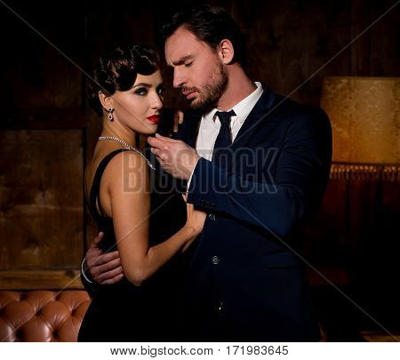 Vamp woman with red lips looking at camera and dreaming about marrying millionaire man. Handsome businessman hugging lady and touching her chin.