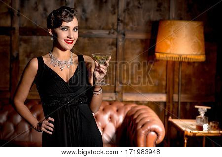 Vamp lady with red lips posing with glass of cocktail in restaurant. Elegant rich lady in black dress posing with her hand on hip. Wealth concept.