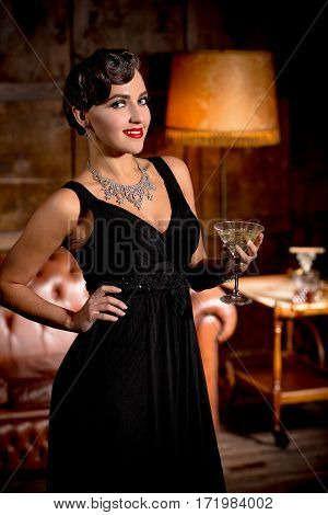 Vamp lady in black dress posing with her hand on hip. Beautiful woman with red lips looking at camera and holding glass of alcohol cocktail.