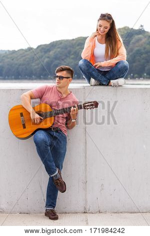 Love romance relationship music concept. Cheerful couple spending time on coast. Young boy is playing guitar to his girl.