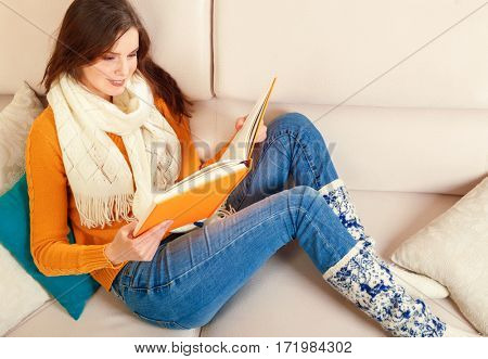 Girl reads a book lying at white soft sofa. Culture lifestyle. Leisure. Young woman reading art literature