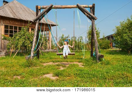 Rural landscape with wooden swings in the garden