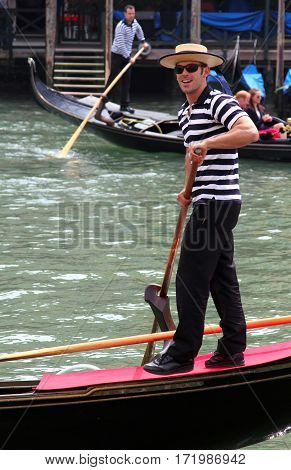 Venice, Italy - Apr 14, 2013: Smiling Young Gondolier  In Traditional Dress On His Gondola On The Gr