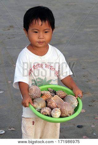 Mui Ne, Vietnam - Feb 20, 2009: Little Vietnamese Boy Selling Shells On The Beach. Children From Poo