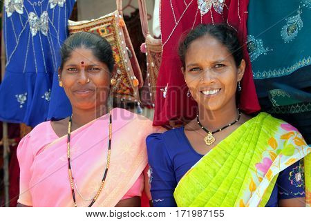 Goa, India - Feb 13, 2008: Indian Women In Colorful Saris Selling Clothes On The Beach