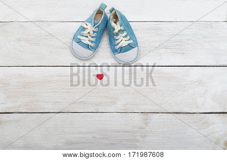 Blue shoes for a small baby on a wooden background. View from above