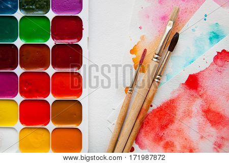 Top View Palette Of Watercolor Paints, Brushes And Paper For A Water Color On White Background, Clos