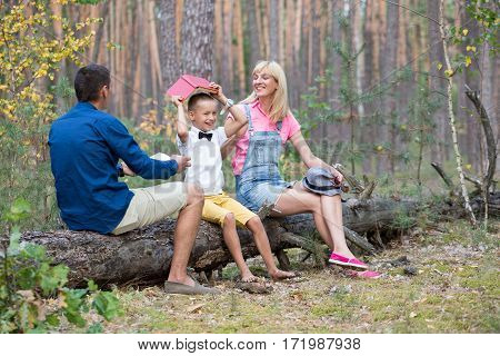 Young family relaxing on the nature. Parents spend time with his son in the fun atmosphere.