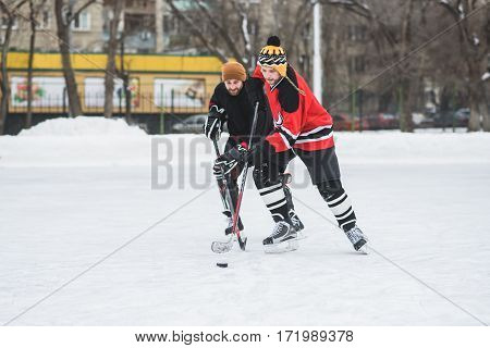 Two Ferocious Hockey Players Fighting For Puck