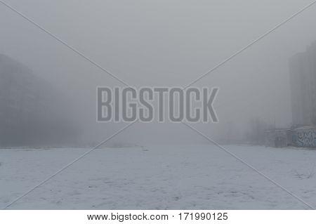Foggy morning. Multi-storey building in the fog. Snowy morning and fog.