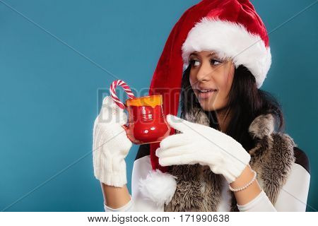 Christmas time concept. Mixed race teen girl wearing santa helper hat holding red mug with hot beverage and striped candy cane studio shot on blue