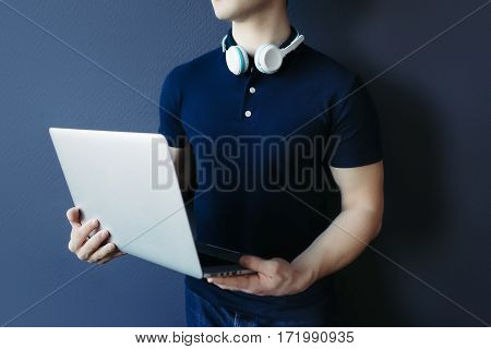 Young athletic man in t-shirt with headphones and laptop. Studuo, unrecognisable.