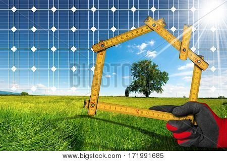 Hand with work glove holding a wooden ruler in the shape of house with a solar panel and sun rays in countryside. Concept of ecological house