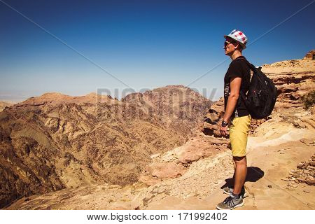 Hipster traveler contemplate impressive mountains landscape. Man with backpack and hat standing alone on top mountain enjoy freedom. Wanderlust travel concept. Atmospheric epic moment. Copy space.
