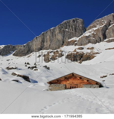 Timber hut and mountain. Winter scene in Braunwald Swiss Alps.